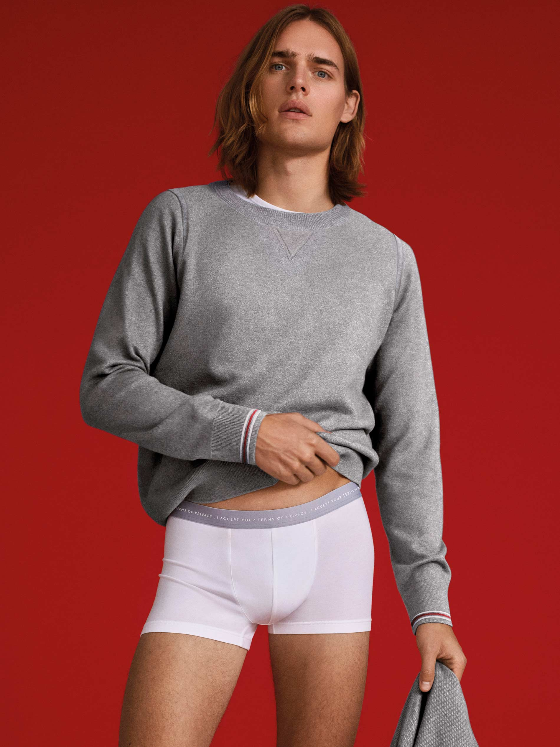 """Man wears shorties with slogan """"I accept your terms of privacy"""" on the waistband from the basics range of the RE:THINK series 