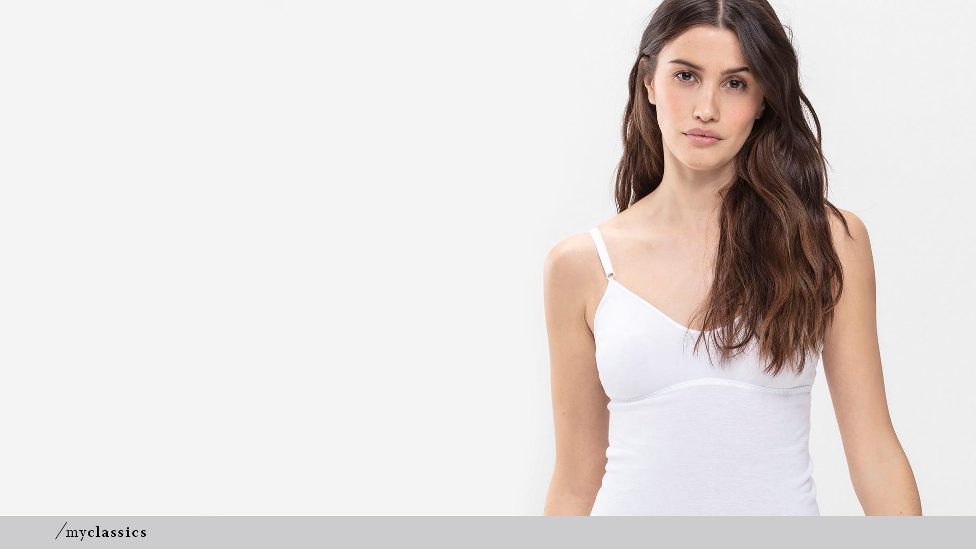 Dunkelhaarige Dame trägt weißes BH-Hemd ohne Seitennähte aus Peru-Pima Baumwolle der Serie Noblesse von mey®