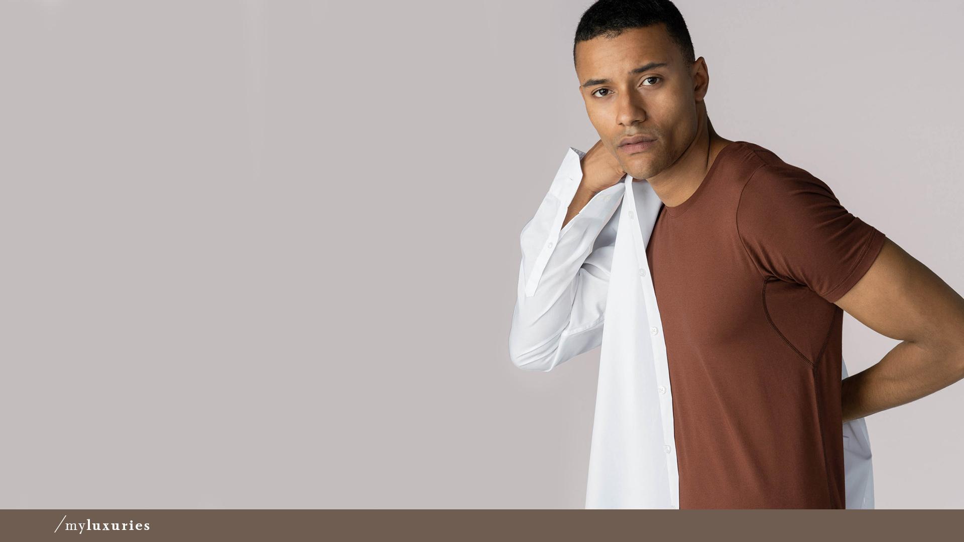 Dunkelhäutiger Mann trägt ein halb ausgezogenes Hemd sowie das Crew-Neck Shirt in der Farbe mokka aus der Serie Business Class von mey®