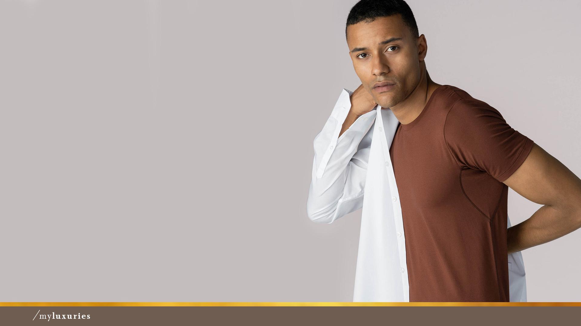 Mann trägt ein halb ausgezogenes, weißes Hemd sowie das Crew-Neck Shirt in der Farbe Medium Skin aus der Serie Business Class von mey®