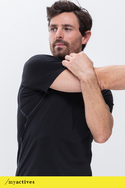 Man wears a black T-shirt from the Performance series while performing a stretching exercise for the arms | mey®