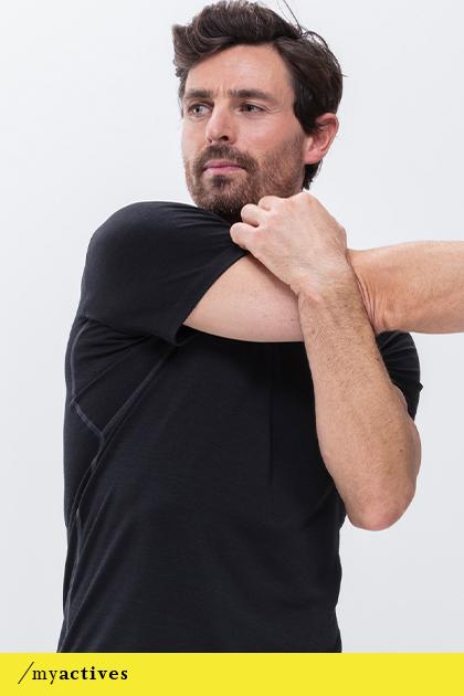 Mann trägt schwarzes T-Shirt aus der Serie Performance von mey bei einer Dehnübung für die Arme   mey®