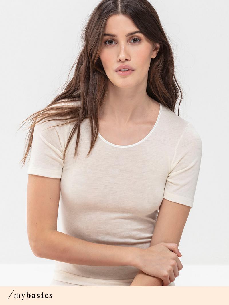 Dunkelhaarige Dame mit langen Haaren trägt weißes Shirt mit Wolle-Seide-Mix aus der Serie Exquisiste von mey®