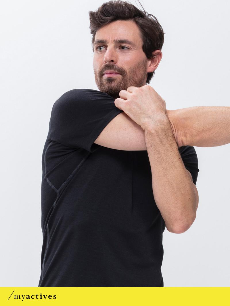 Mann trägt das schwarze T-Shirt bei einer Dehnübung für die Arme aus der Serie Performance von mey®