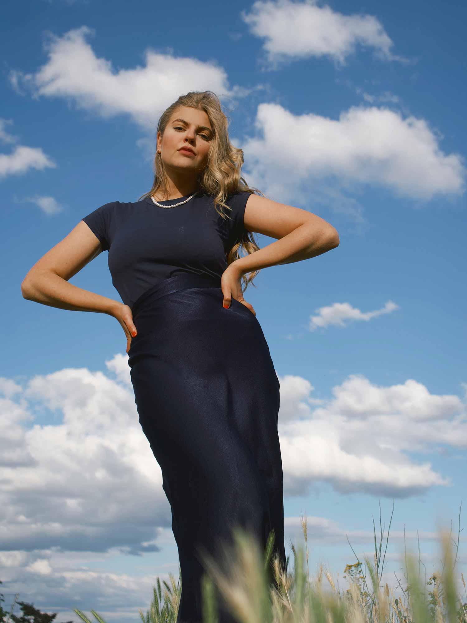 Bij een glanzende satijnen rok combineert Franziska Nazarenus een hooggesloten katoenen shirt in navy | mey®