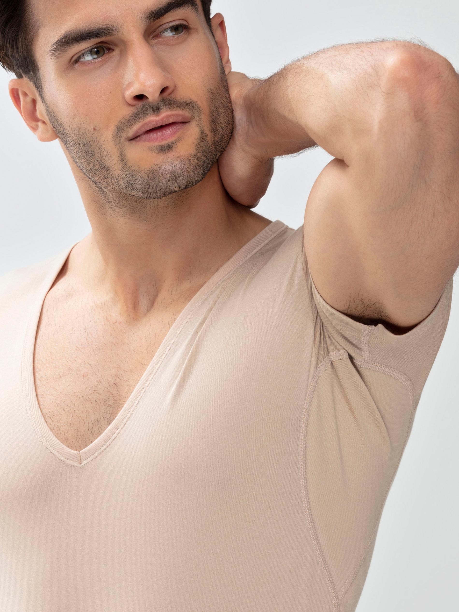 mey® Modelbild mit Mann, der das Drunterhemd in der Farbe Light Skin trägt, der Arm ist nach oben angewinkelt und die Einsätze unter den Achseln mit den Silberionen sind zu sehen