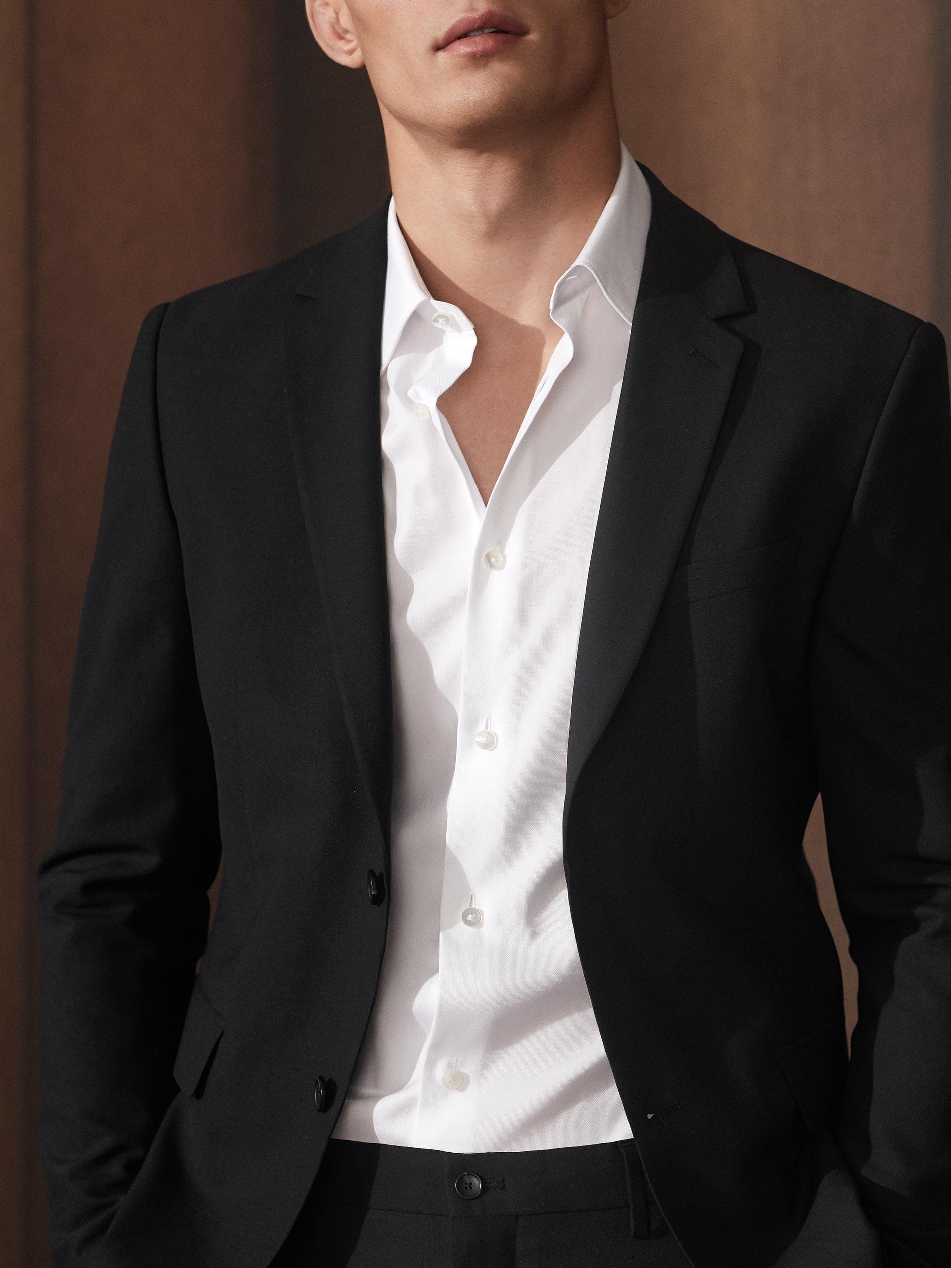 Mann trägt ein Jacket, eine Anzughose und ein weißes Hemd, es sind zwei Hemd-Knöpfe geöffnet, seine Brust ist sichtbar, aber kein Unterhemd ist zu erkennen