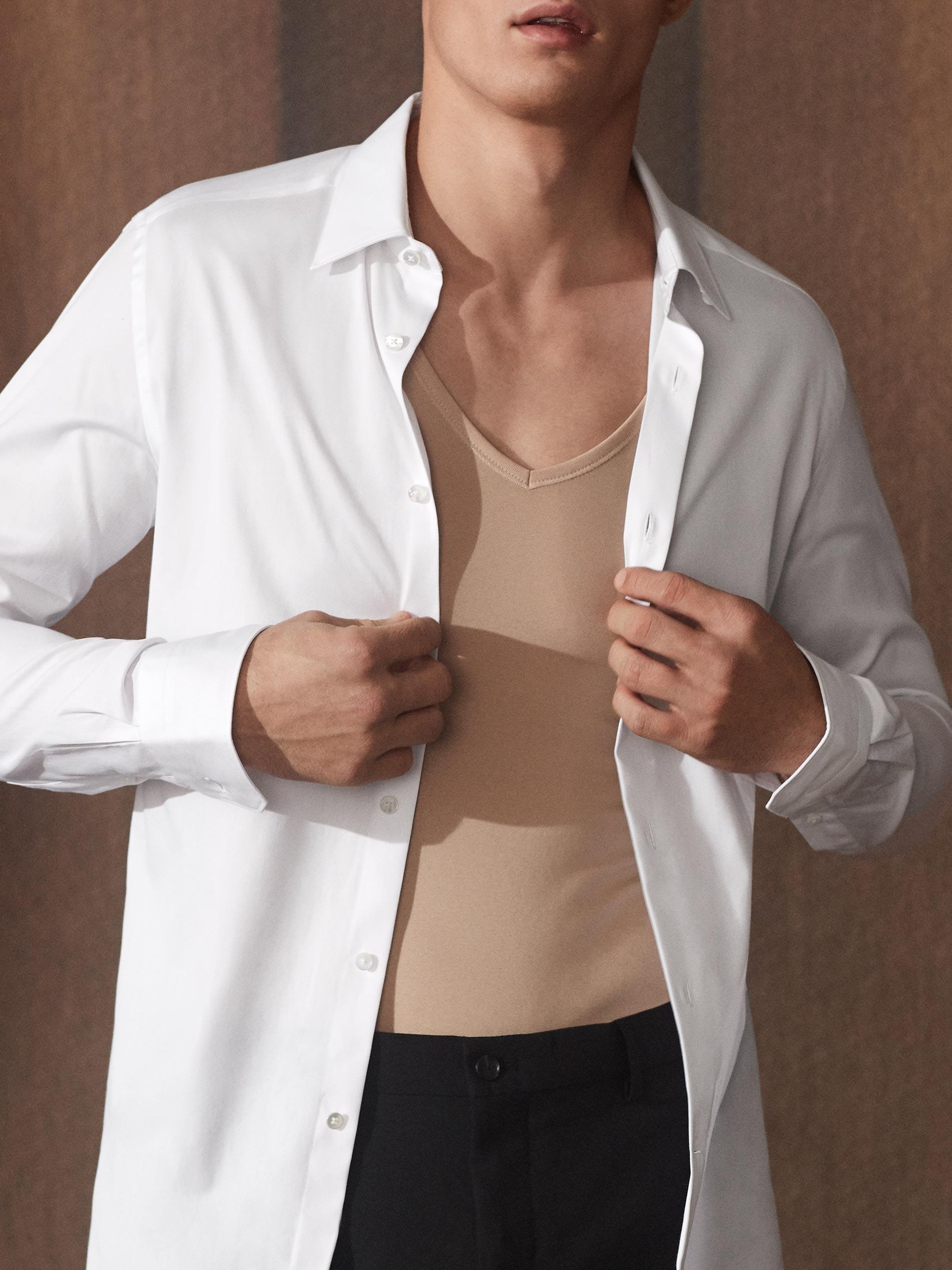 Mann trägt eine Anzughose und ein komplett geöffnetes weißes Hemd, er möchte es gerade ganz ausziehen, das Drunterhemd in der Farbe Light Skin mit dem extra-tiefen V-Ausschnitt ist sichtbar