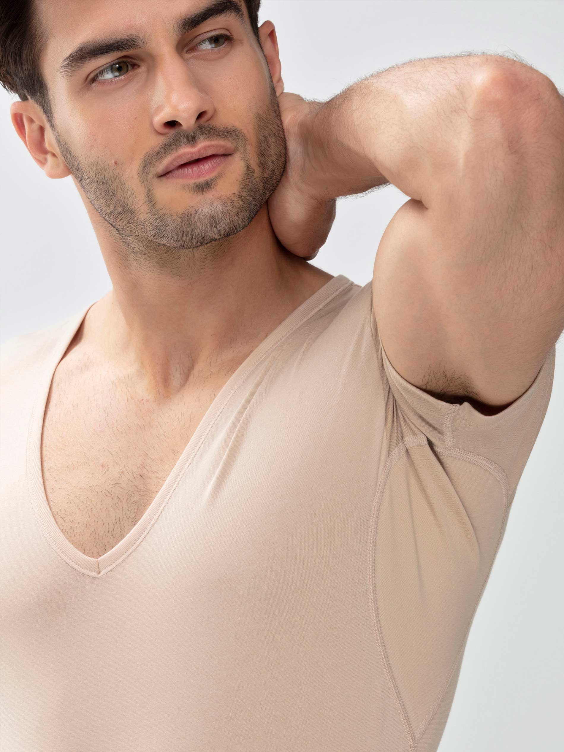Man wears the undershirt in the colour Light Skin; his arm is angled upwards and the inserts with silver ions are visible under the arms. | mey®