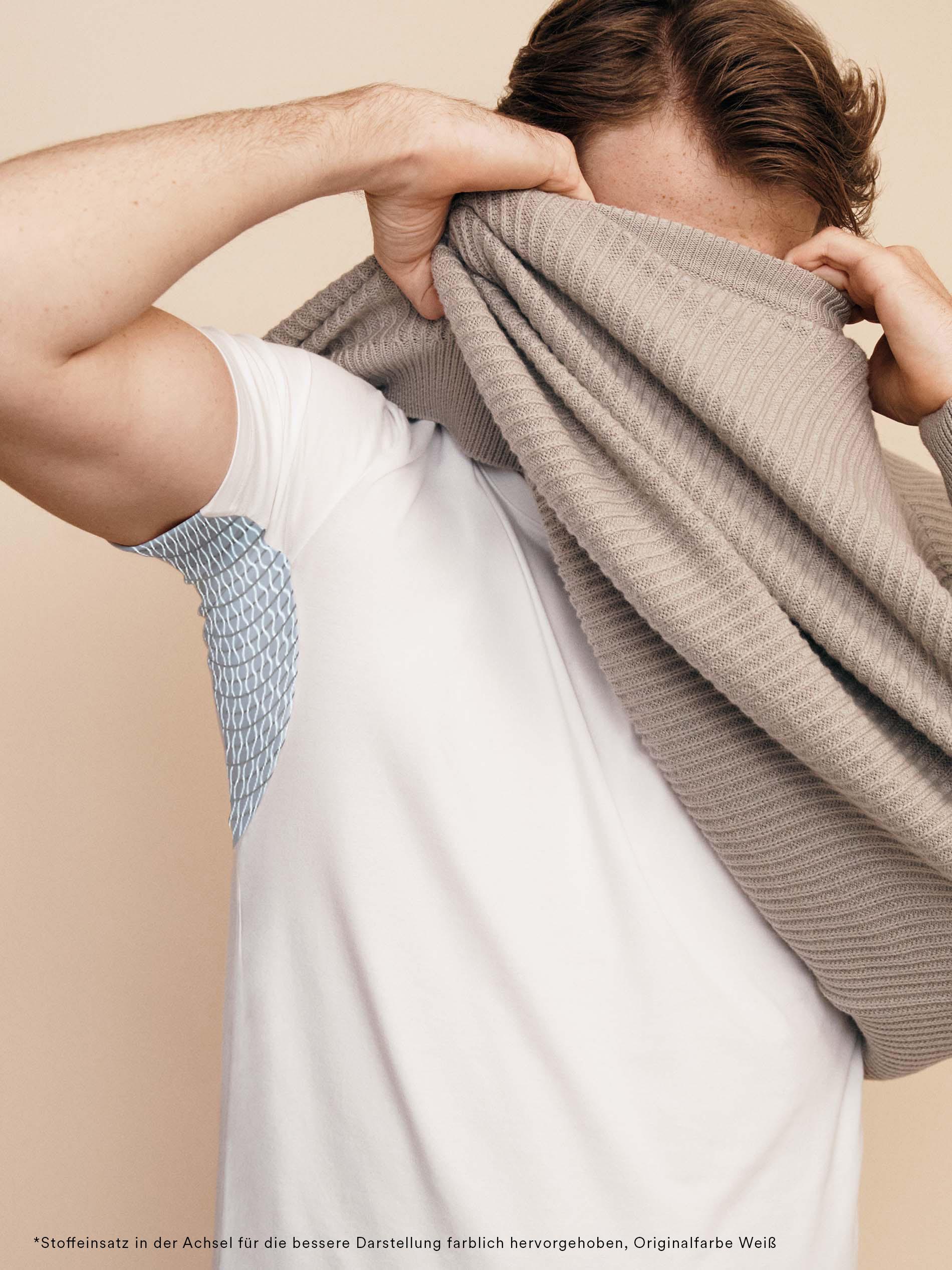 Modelbild mit Mann, der das Hybrid T-Shirt in der Farbe Weiß trägt und sich gerade einen beigen Pullover auszieht. Der Einsatz in der Achsel ist farblich hervorgehoben | mey®