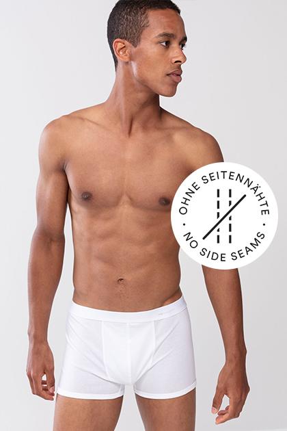 Mey® Serie Casual Cotton, weiße Basic-Shorty am Model, mey® Icon für keine Seitennähte, zwei Nähte sind durchgestrichen