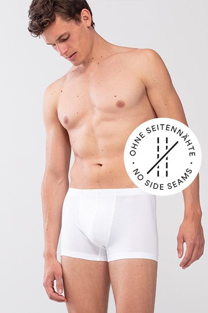 Mey® Serie Casual Cotton, weiße Shorty am Model, mey® Icon für keine Seitennähte, zwei Nähte sind durchgestrichen