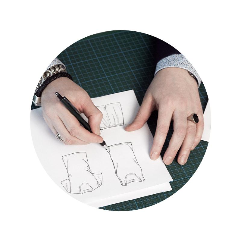 Mey® Serie Dry Cotton Functional, zwei Hände, die Zeichnungen von den Produkten anfertigen