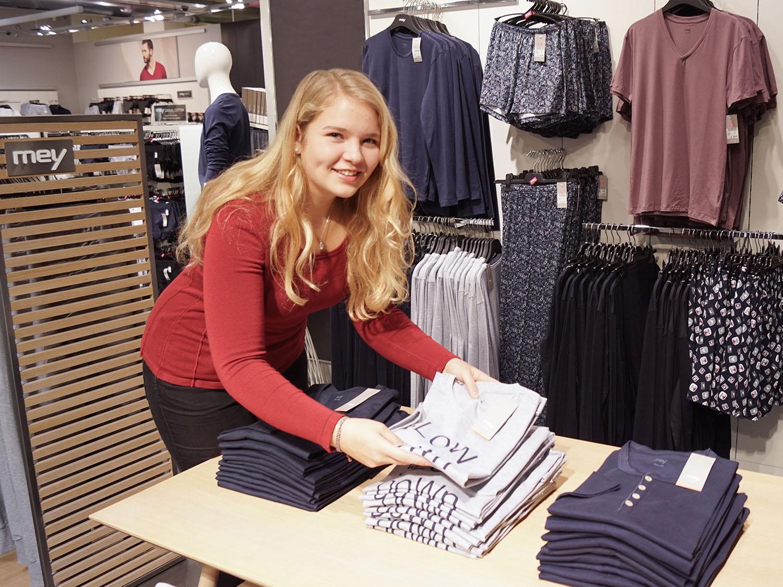 Die Auszubildende als Kaufmann im Einzelhandel dekoriert einen Ladentisch in Albstadt, Deutschland | mey®