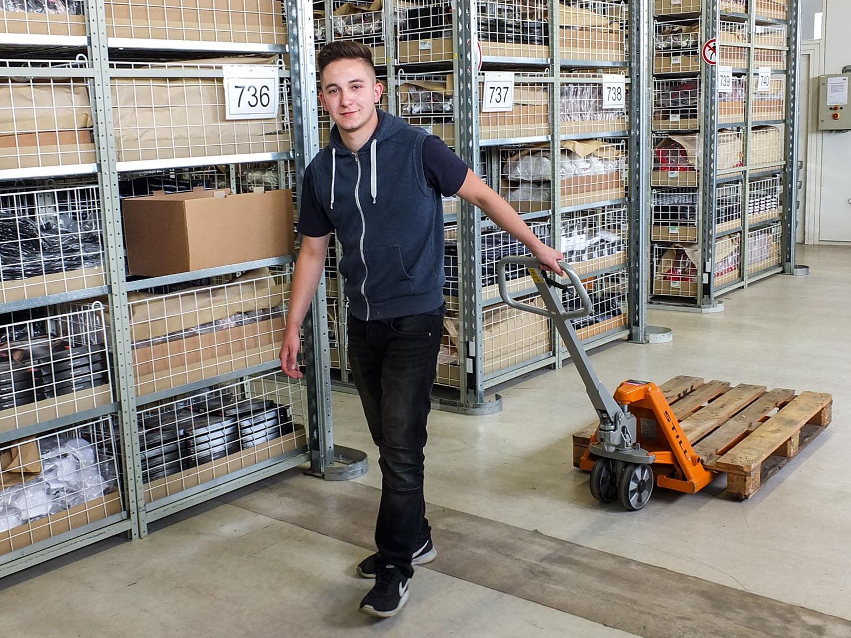 Der Auszubildende als Fachkraft für Lagerlogistik bewegt einen leeren Palettenwagen durch das Lager in Bitz, Deutschland   mey®