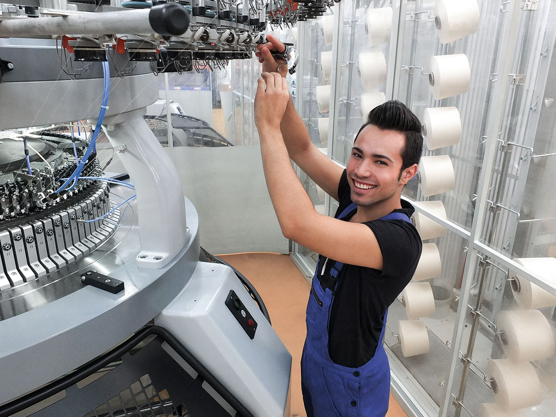 Der Auszubildende als Produktionsmechaniker Textil behebt eine Störung an der Fadenführung der Strickmaschine | mey®