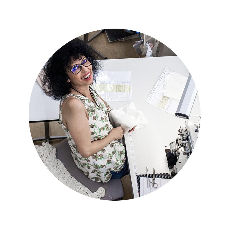Mitarbeiter Portrait von Anna-Maria Leonardi von oben an der Nähmaschine mit einem weißen Stoff in der Hand | mey®