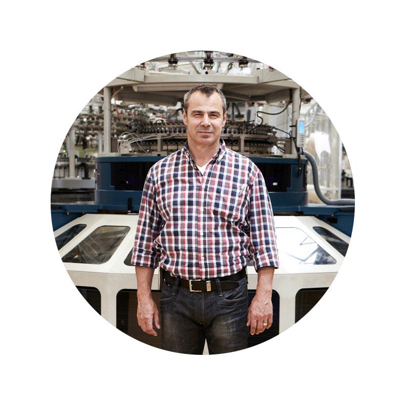 Mitarbeiter Portrait von Holger Teufel in der Strickerei vor einer Strickmaschine | mey®
