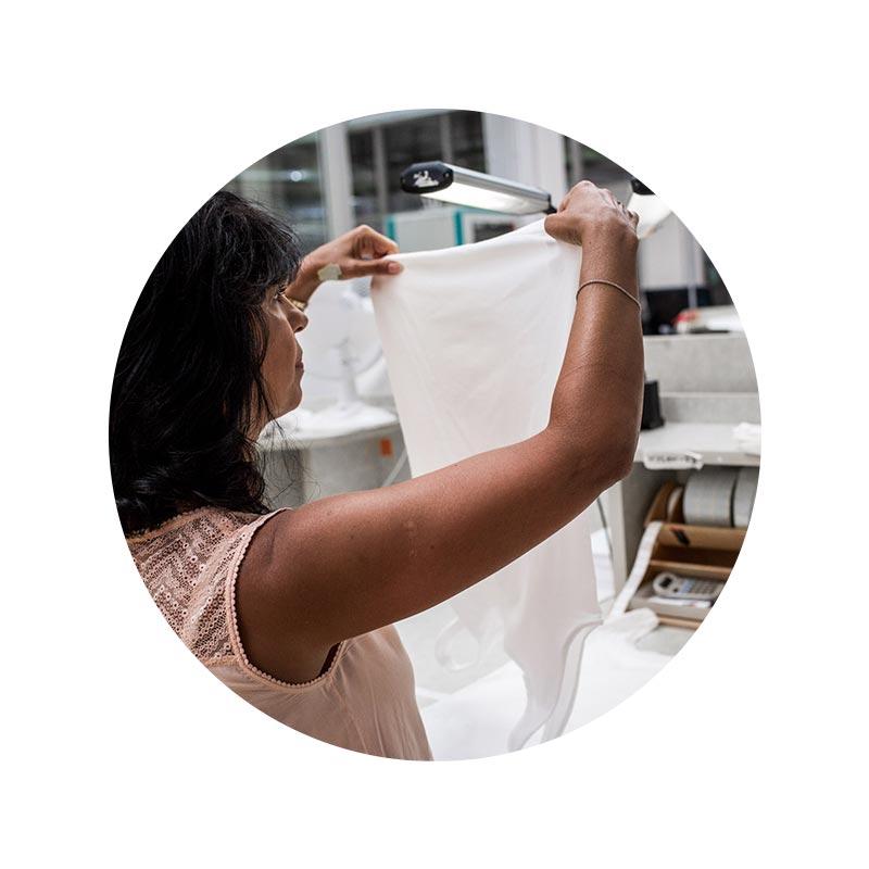 mey® Mitarbeiter Portrait von Emilia Antenucci im Bereich Qualitätskontrolle bei der Überprüfung eines Top-Saums auf Qualitätsmängel