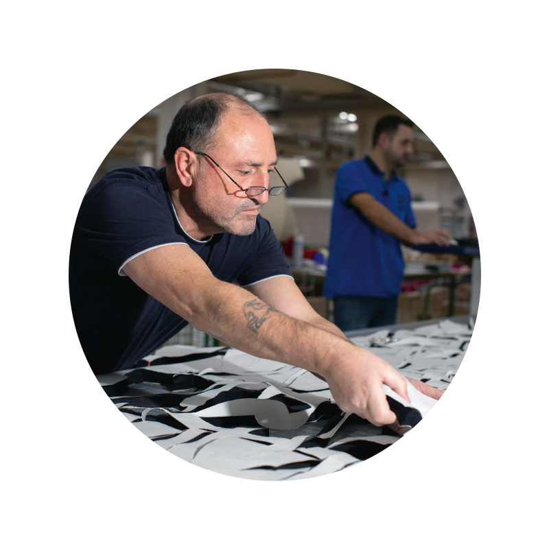 Mey® Mitarbeiter im Zuschnitt entnimmt die zugeschnittenen Stoffstücke vom Schneidetisch