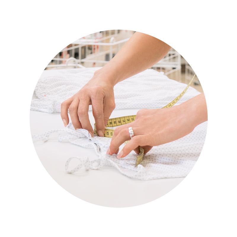 Mey® Mitarbeiterin an der Qualitätskontrolle, Hände mit gelbem Maßband und einem gepunkteten Top