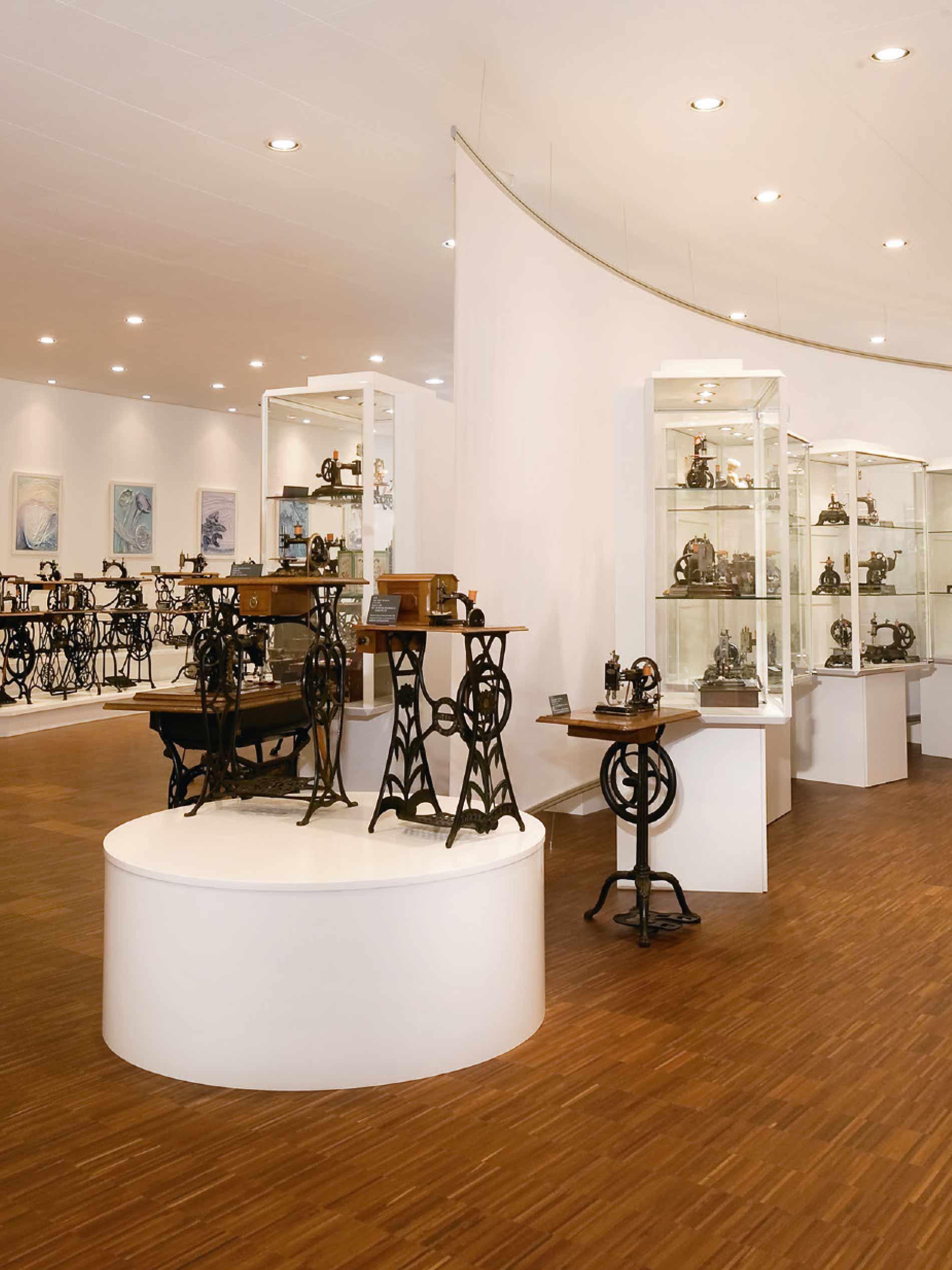 Einblick in das Nähmaschinenmuseum mit kleinen Standnähmaschinen auf einem Podest und Vitrinen im Hintergrund   mey®