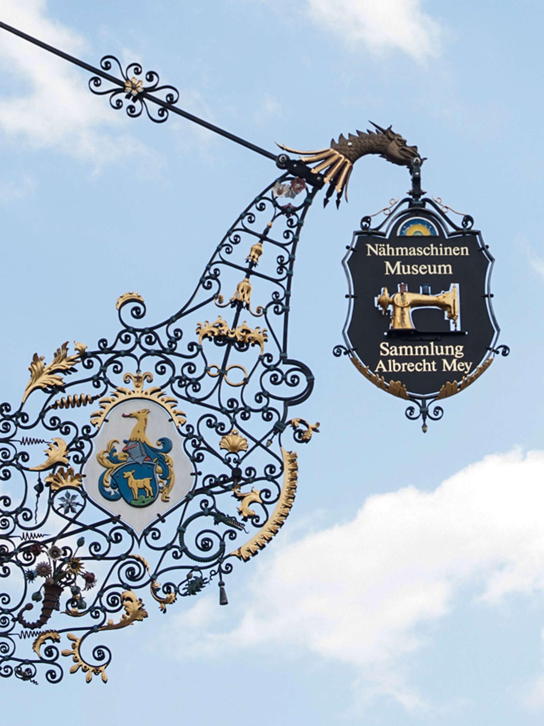 Gusseisernes, mit Blüten verziertes Wappen des Nähmaschinenmuseums Sammlung Albrecht Mey | mey®