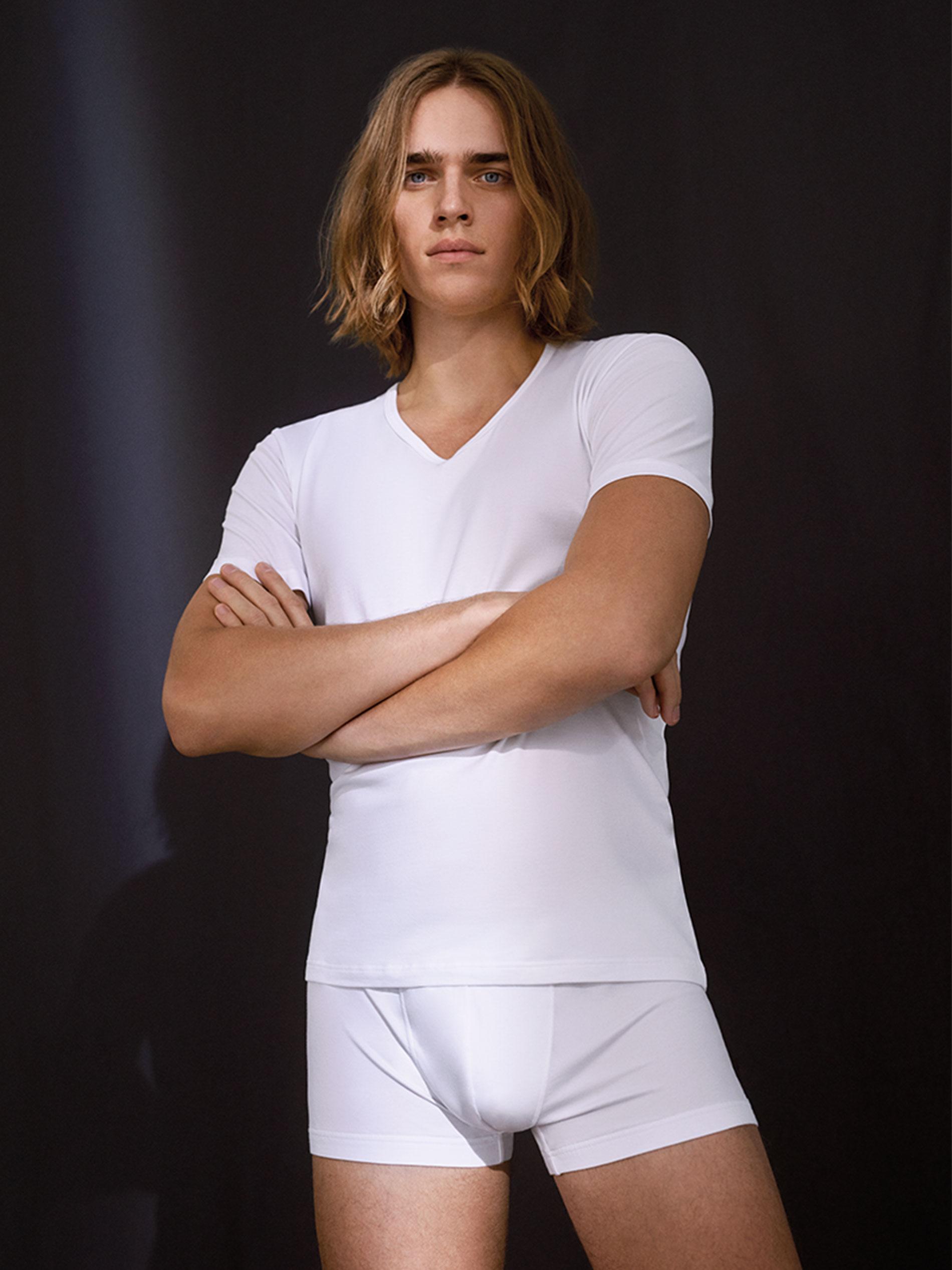 Mann trägt weißes T-Shirt und weißen Shorty aus Bio-Baumwolle der Serie RE:THINK | mey®