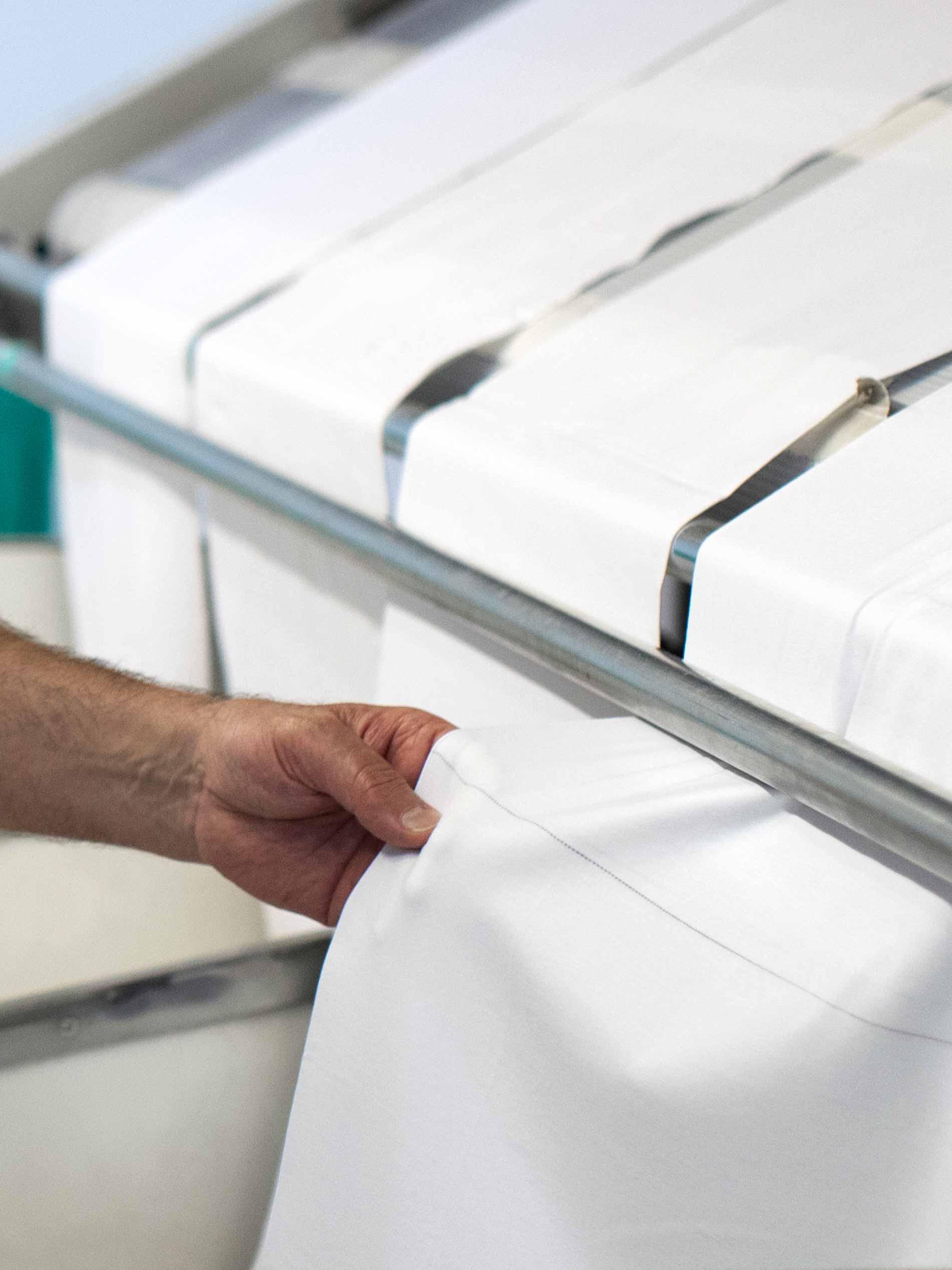 Mitarbeiter kontrolliert den Stoff aus der Kalander-Maschine | mey®