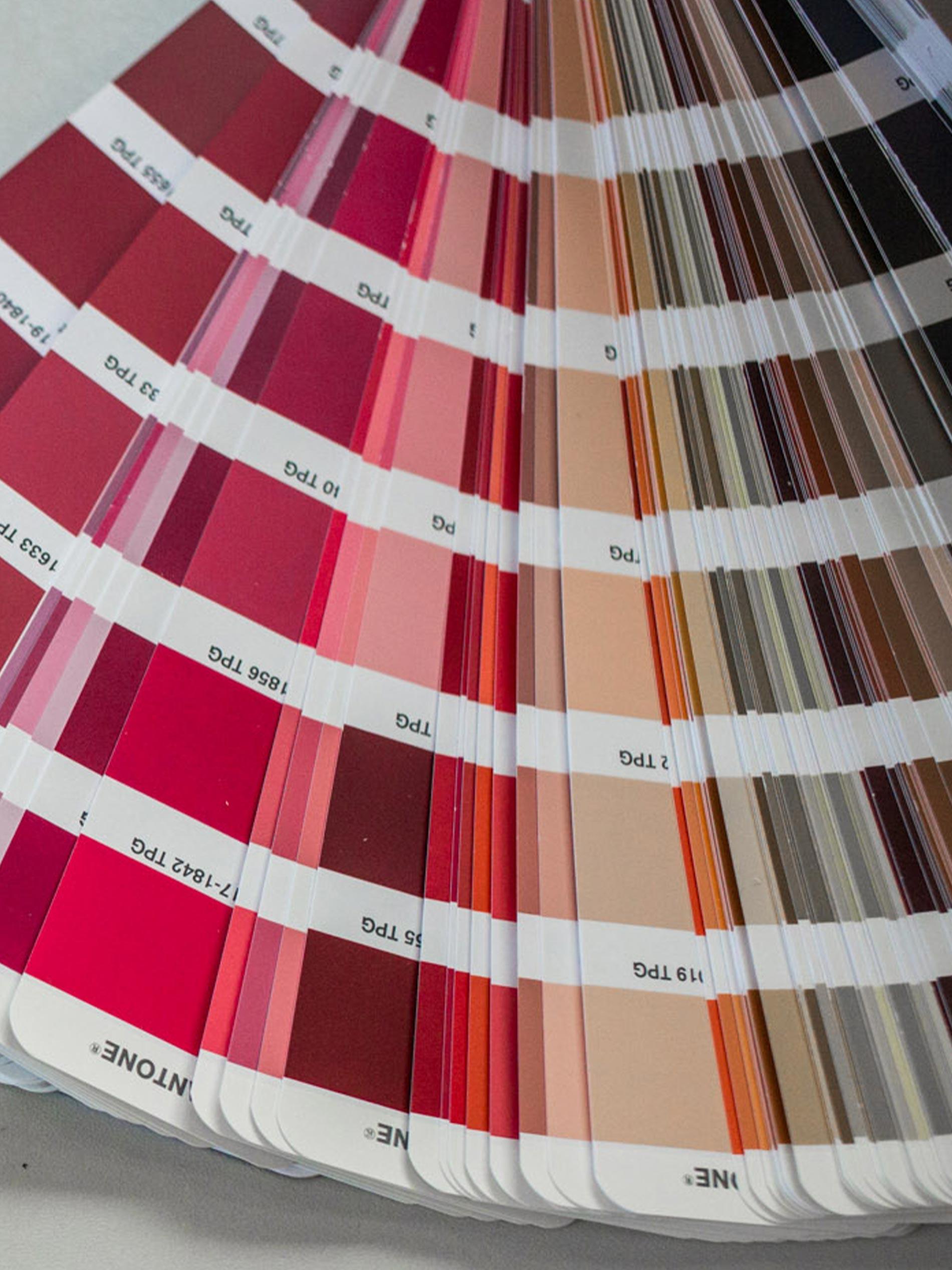 Aufgefächerter Farbfächer von Pantone mit unterschiedlichen Rot- und Pinktönen | mey®