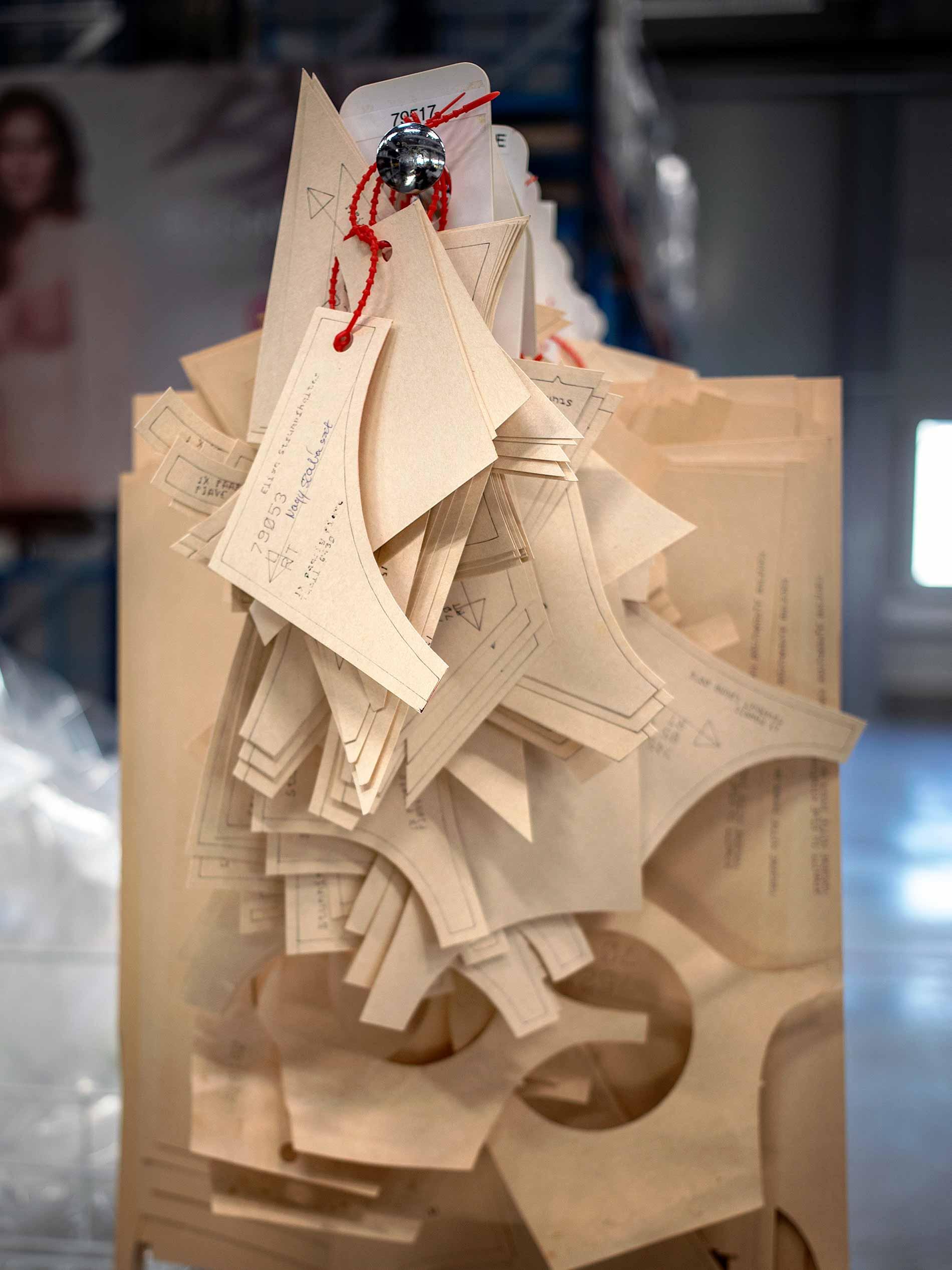 Zuschnitt-Vorlagen aus hellbraunem Karton hängen aufgereiht auf einer Kleiderstange | mey®
