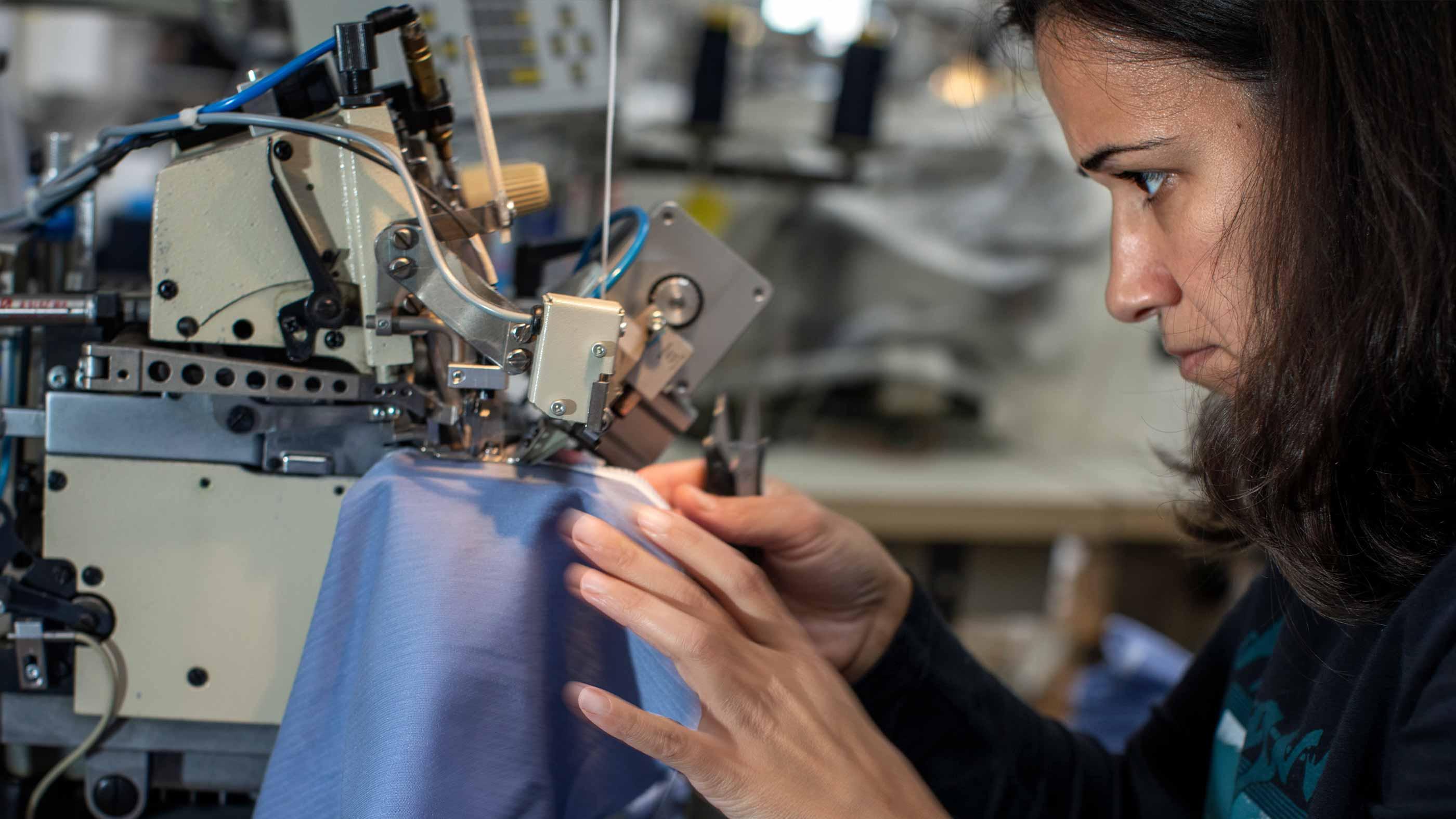 Mitarbeiterin näht konzentriert an einem blauen Wäschestück | mey®