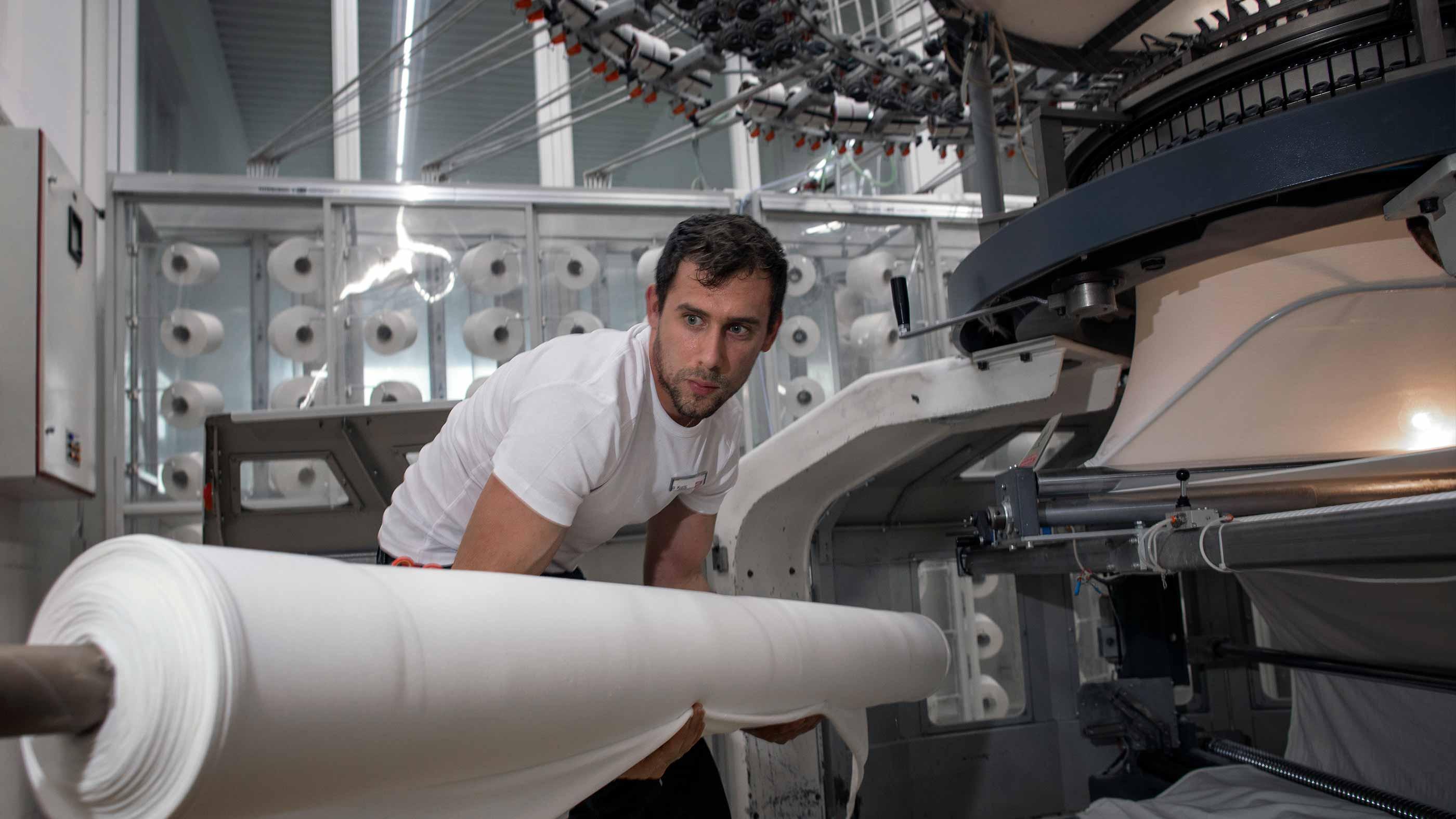 Mitarbeiter entnimmt eine Stoffrolle mit fertig gestrickert Breitware aus der Strickmaschine | mey®