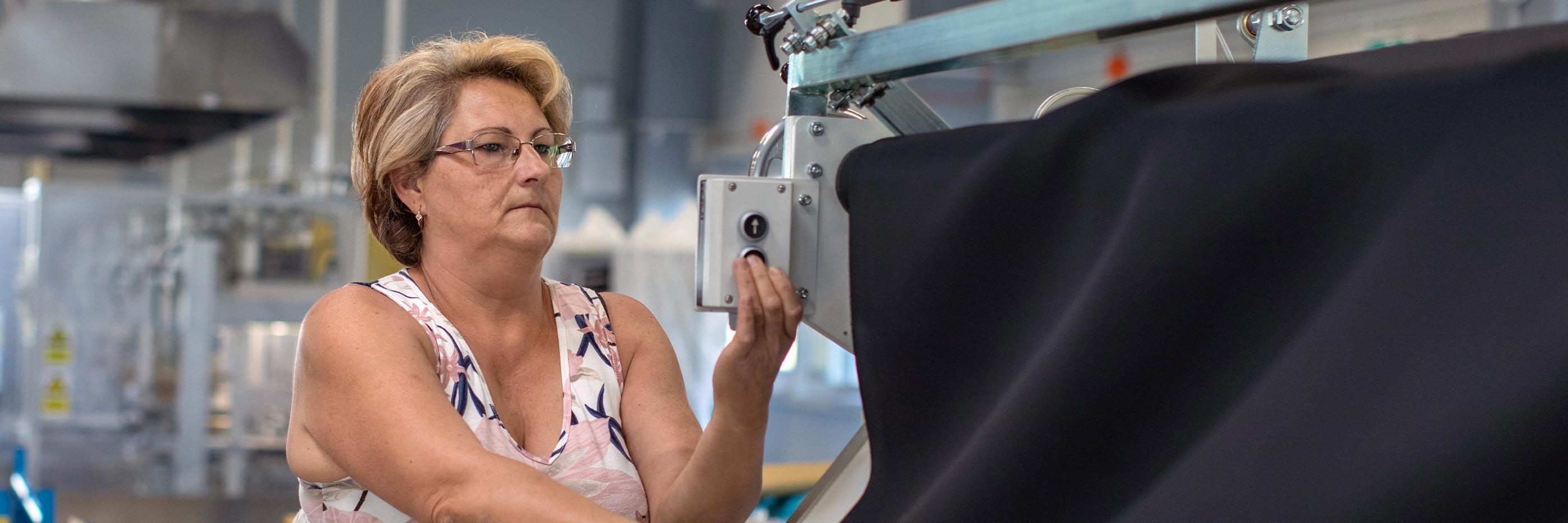 Mitarbeiterin bedient eine Zuschneidemaschine mit dunklem Stoff darauf | mey®