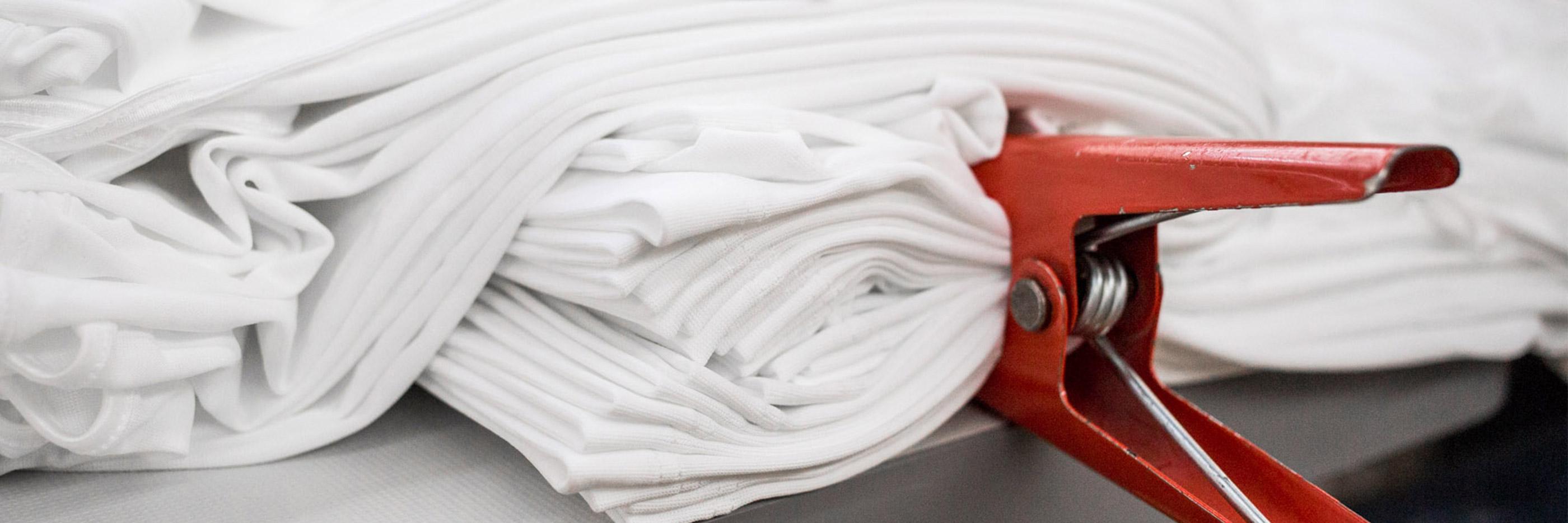 Stoff in weiß in mehreren Lagen gefaltet und mit einer roten Zange fixiert, Vorbereitung für den Kalander-Prozess| mey®