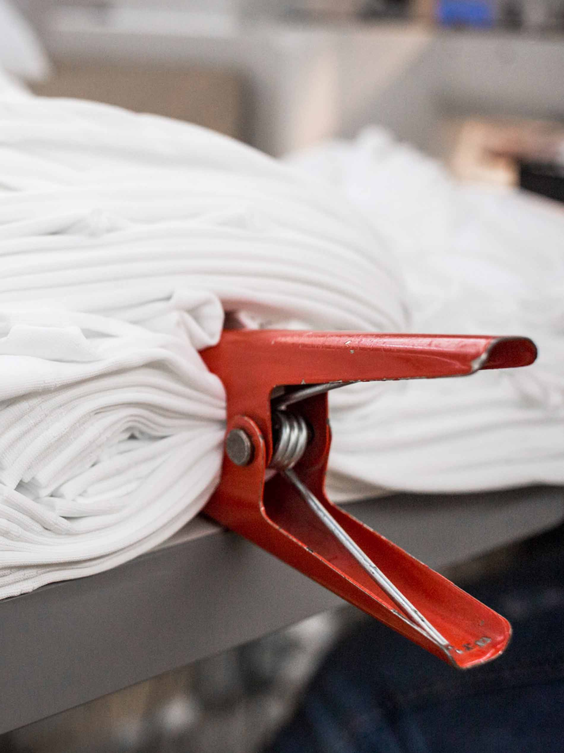 mey® Stoff in weiß mit einer roten Zange fixiert, Vorbereitung für den Kalander-Prozess