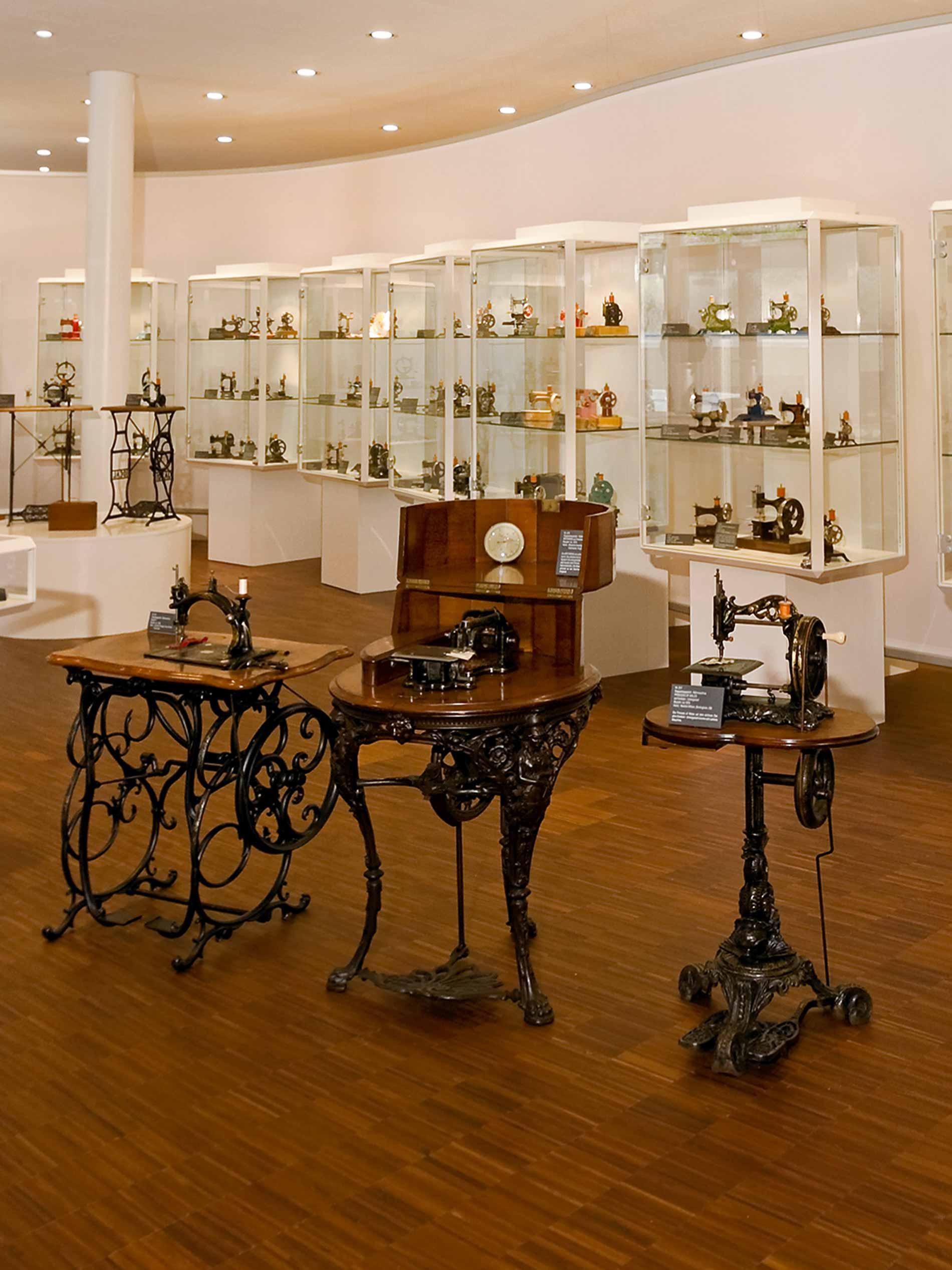 Einblick in das Nähmaschinenmuseum mit drei Standnähmaschinen und Vitrinen im Hintergrund   mey®