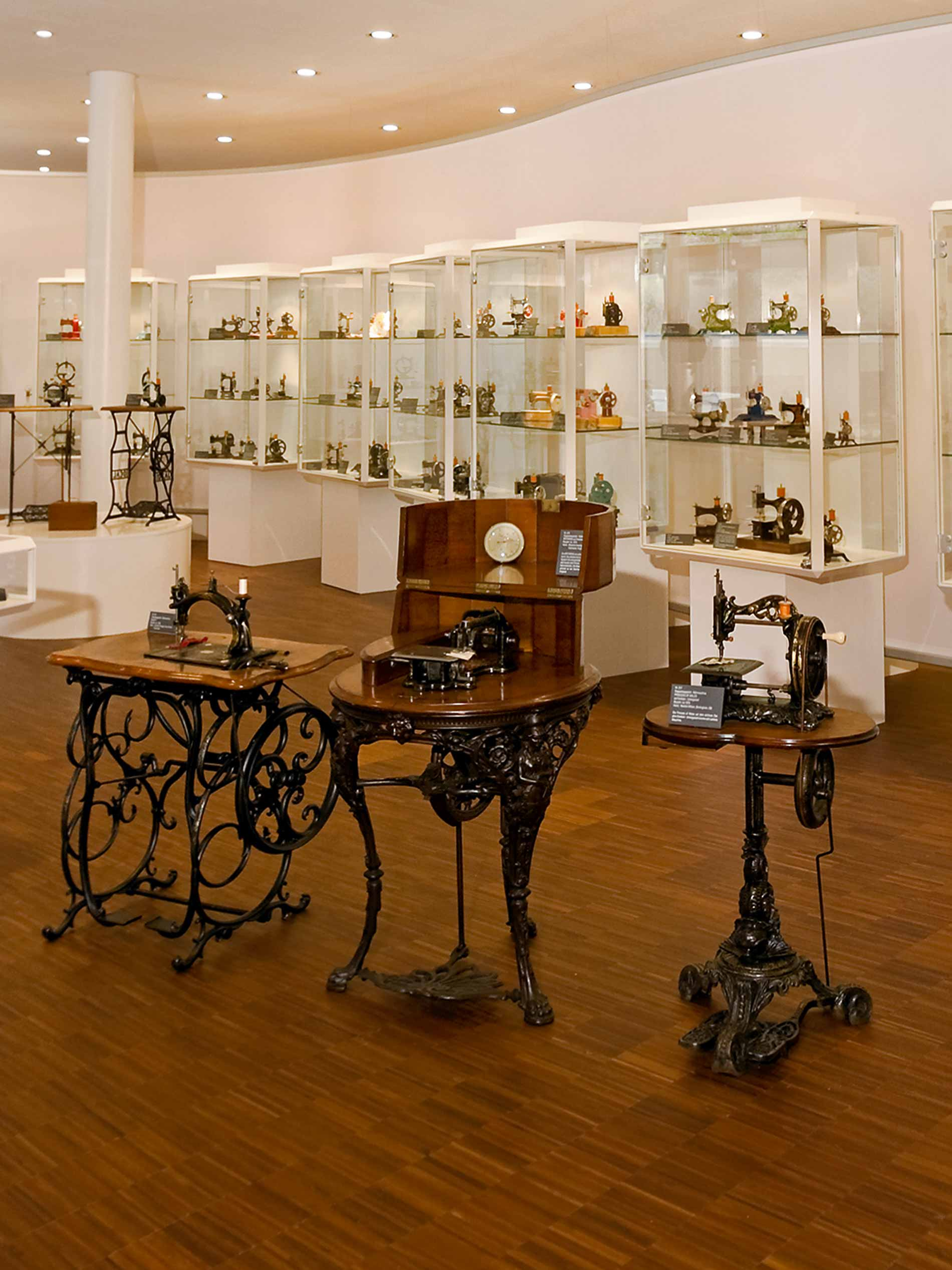 interior of the museum, three historic sewing machines in the foreground and multiple glass vitrines with exhibition pieces in the background | mey®