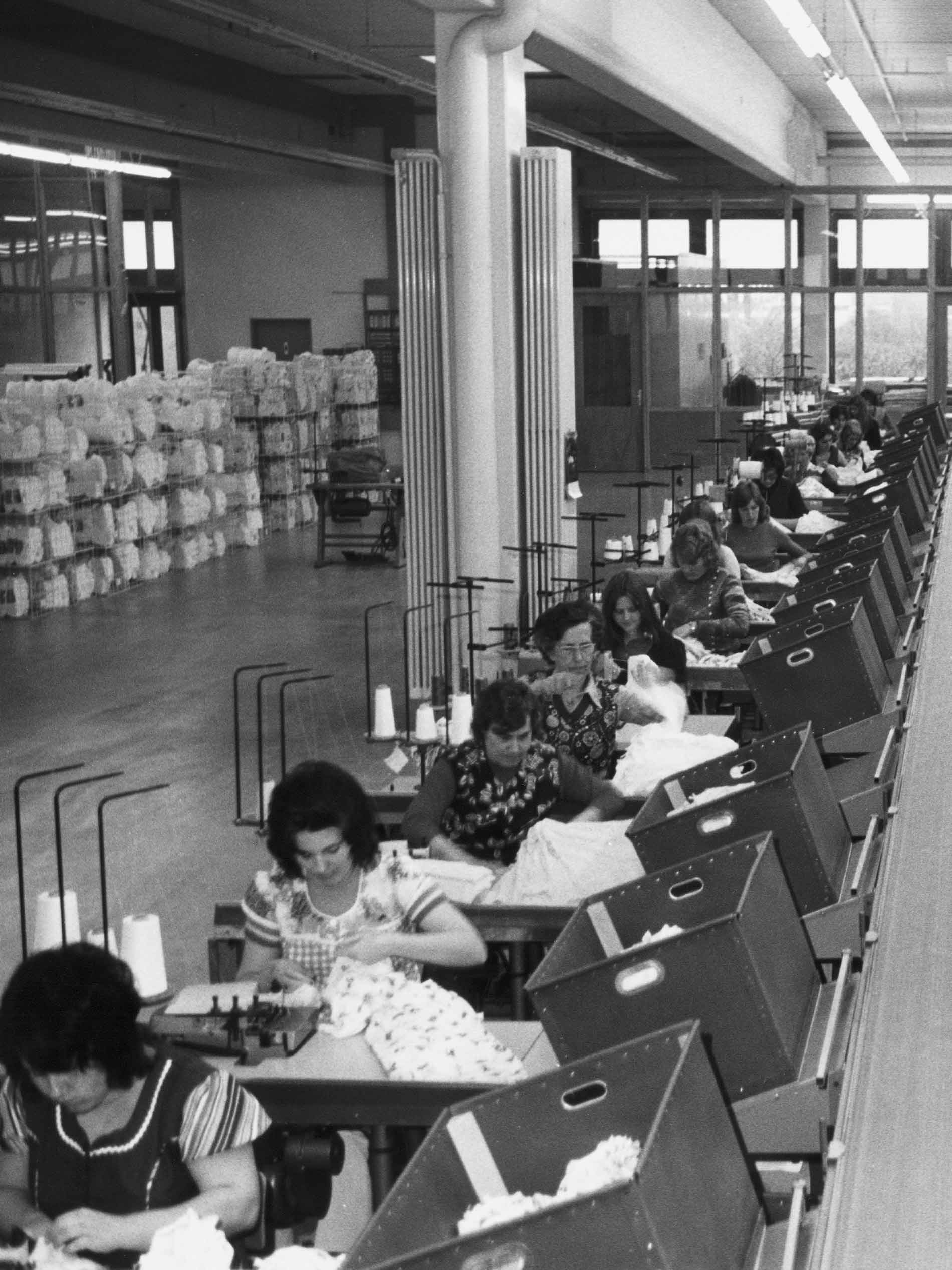 historics photography from the sewing room of the company, black and white photograph with rows of seamstresses and boxes containing products | mey®