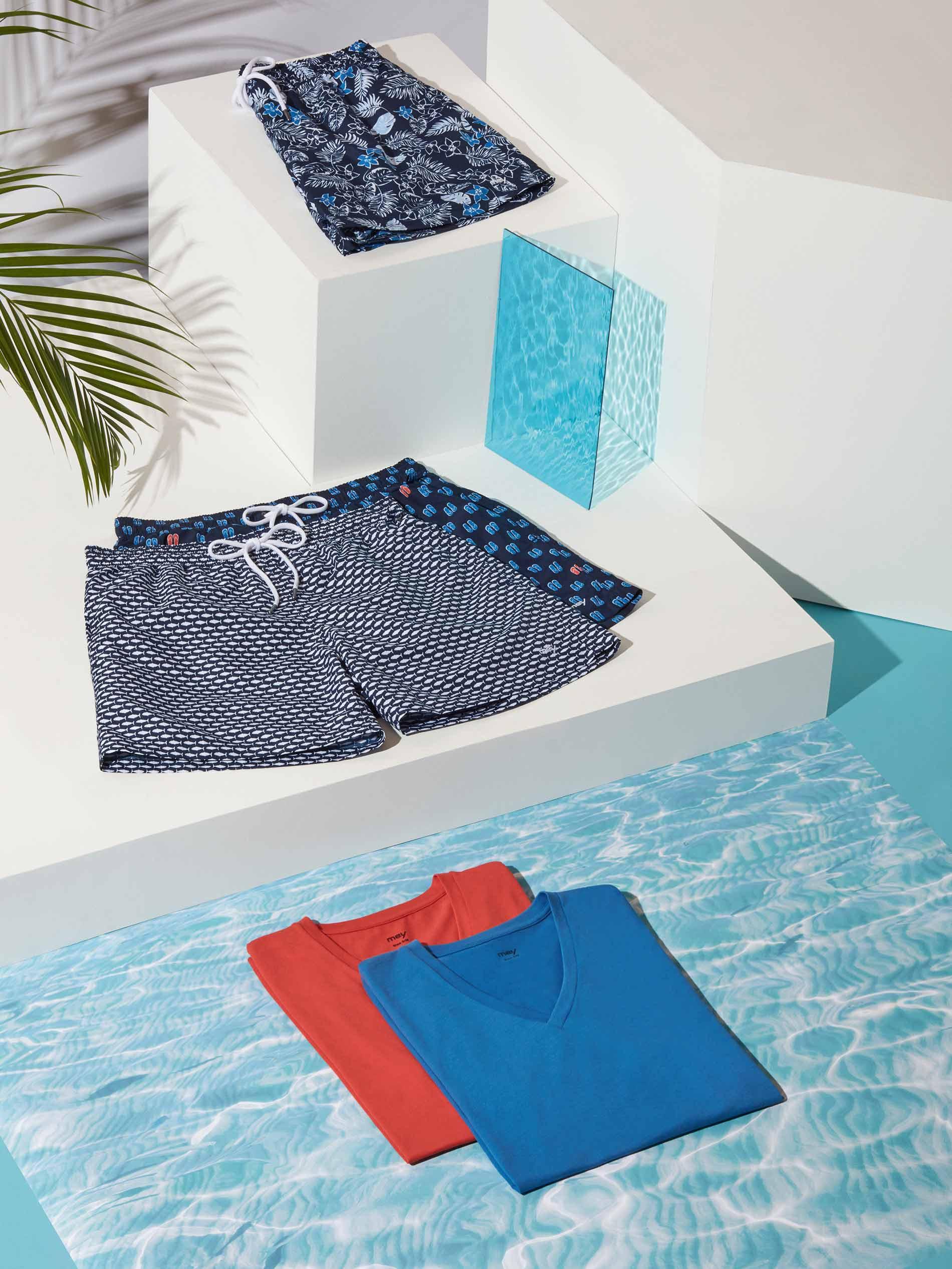mey® Swimwear Badeshorts und farbige T-Shirts arrangiert auf weißen Stelen mit Wasser-Hintergrund und Palmenblatt