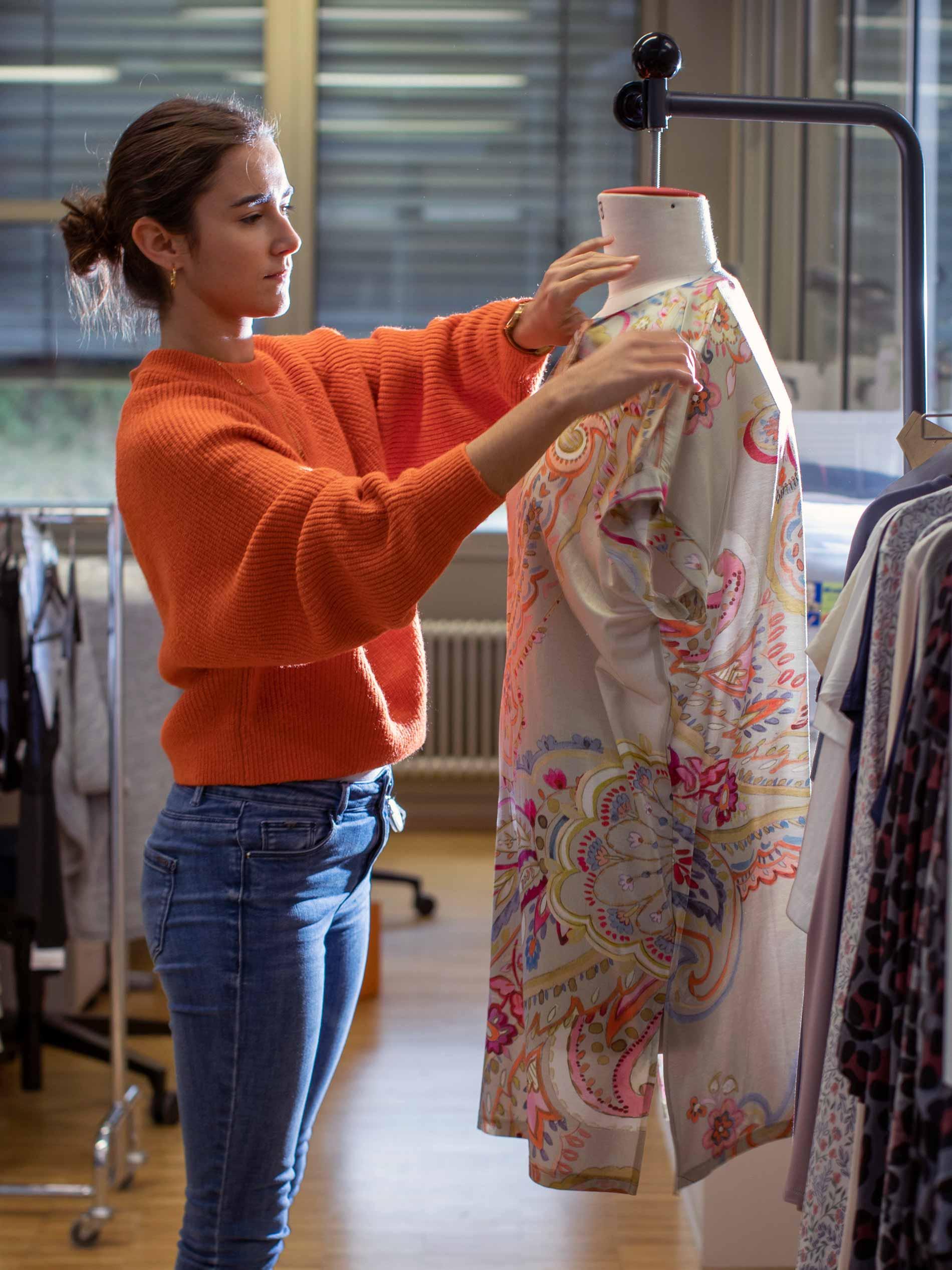 Ontwerpster in damesdesign past een tuniek met patroon op een hangende paspop en controleert het model | mey®