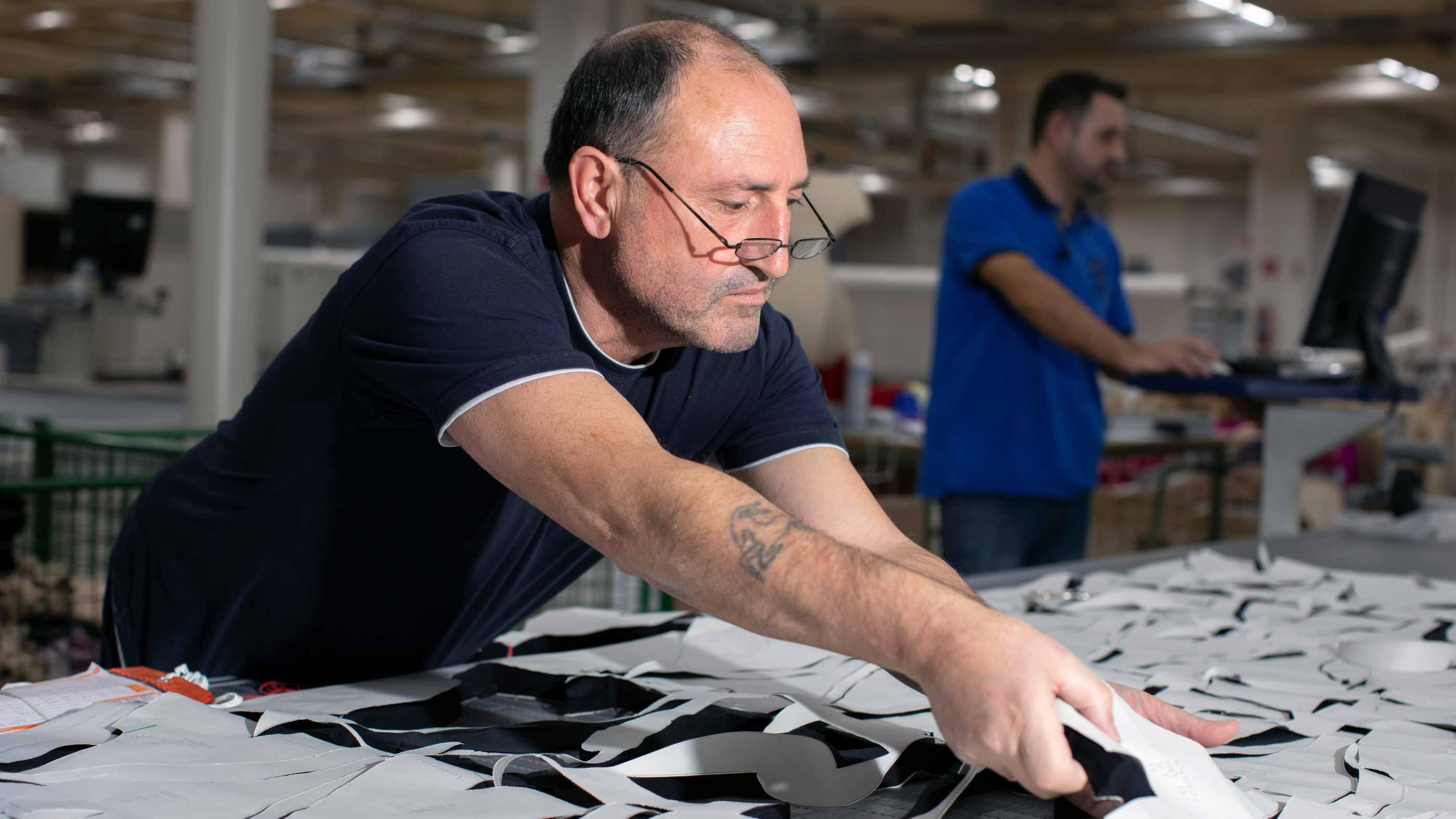 Medewerker neemt de op maat gemaakte stukken stof van de snijtafel van de CAD-cutter | mey®