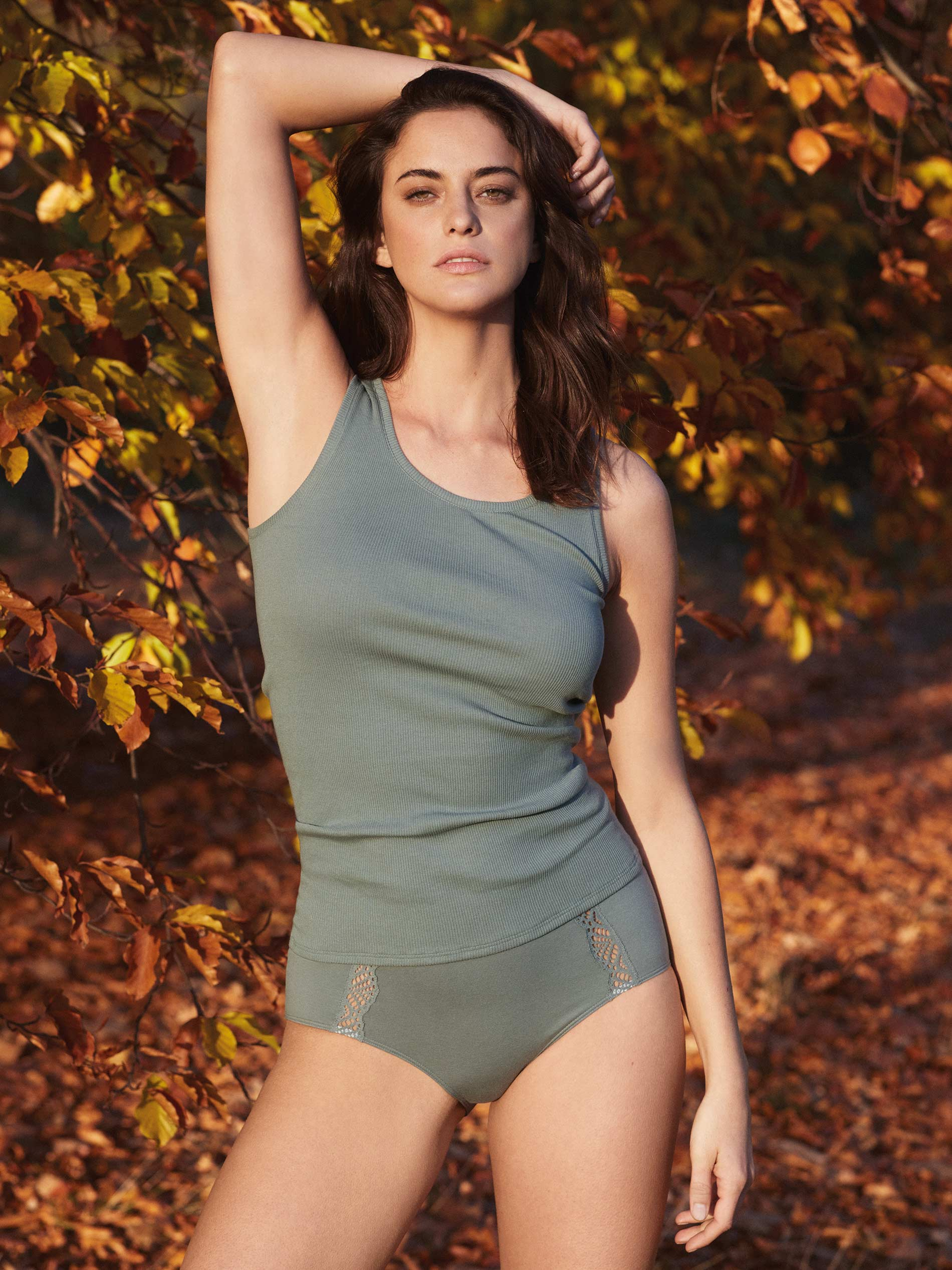 Female model in an autumn forest wears a petrol-coloured fine ribbed top and briefs from the Superfine Organic series   mey®