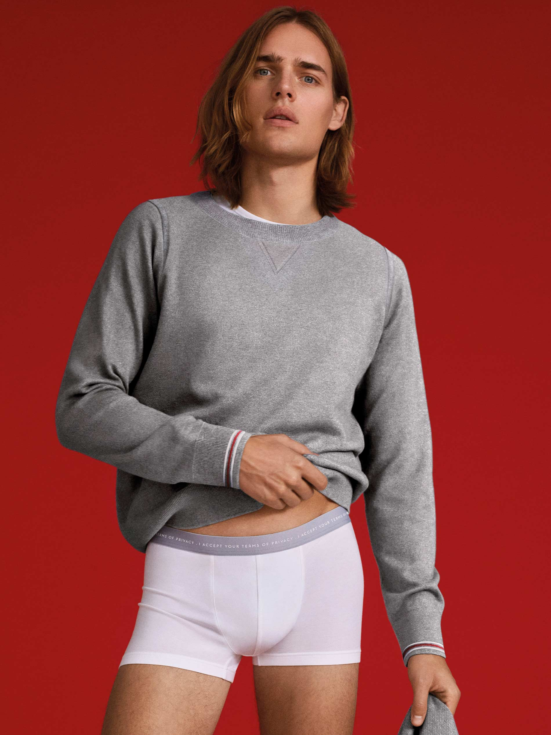 Male model in front of a red background wears a sweatshirt from the Klamila series in mottled grey and shorts from the RE:THINK series with lettering in white   mey®